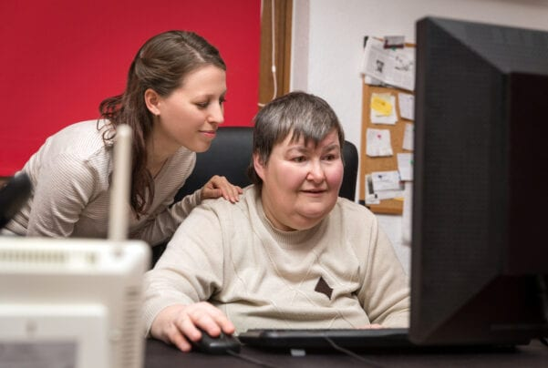 disabled woman and caregiver look at computer