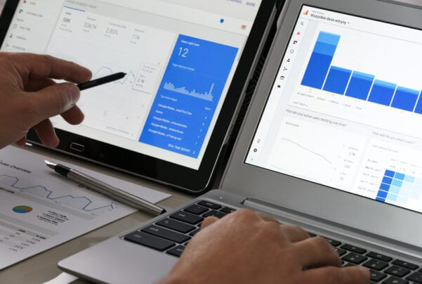 two computers side-by-side with Google Analytics open on the screens and a hand pointing