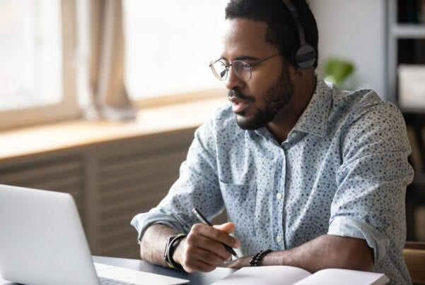 Black man wearing headphones looking at computer and taking notes in a notebook
