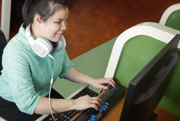 young woman using refreshable braille display to accessibility test a website