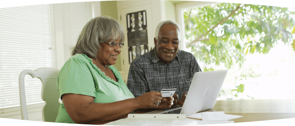 Elderly Black couple looking at laptop and paying bills online in their dining room