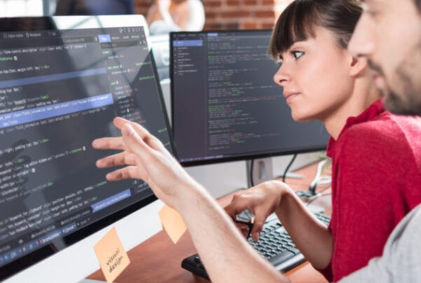 man an woman looking at code on large monitors in office