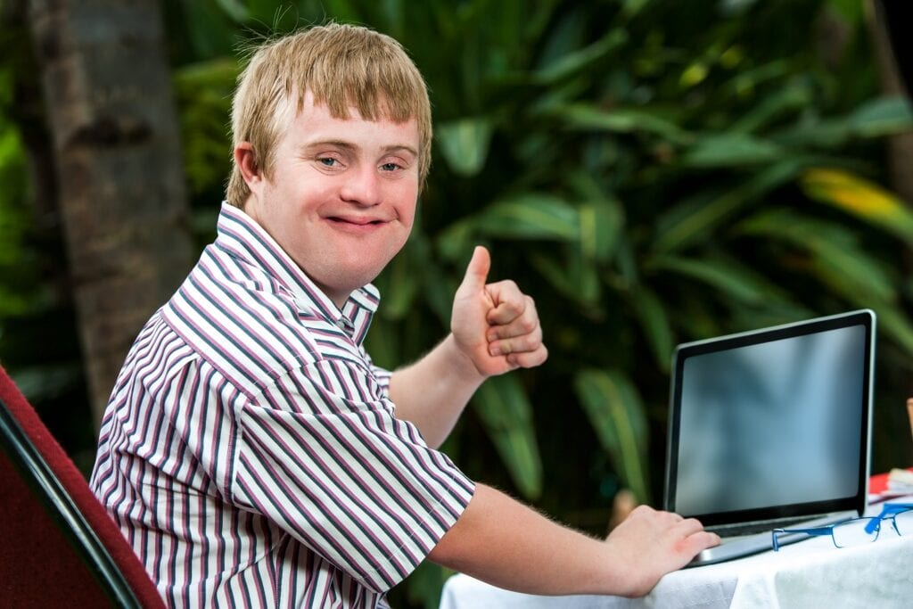 young man with down syndrome using a laptop and giving a thumbs up