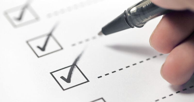 pen checking off list of checkboxes on paper