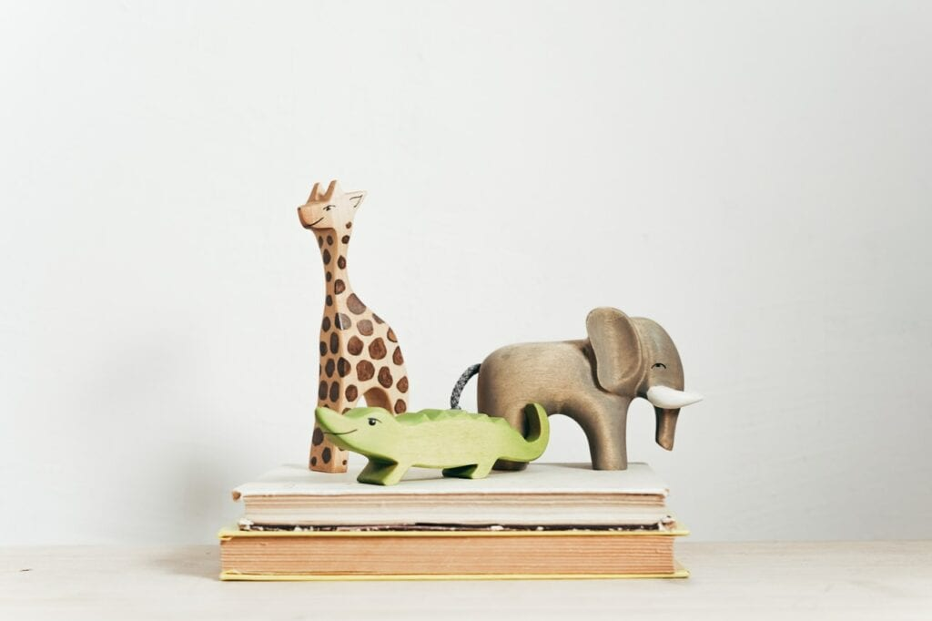hand-carved and painted wooden giraffe, elephant, and alligator toys