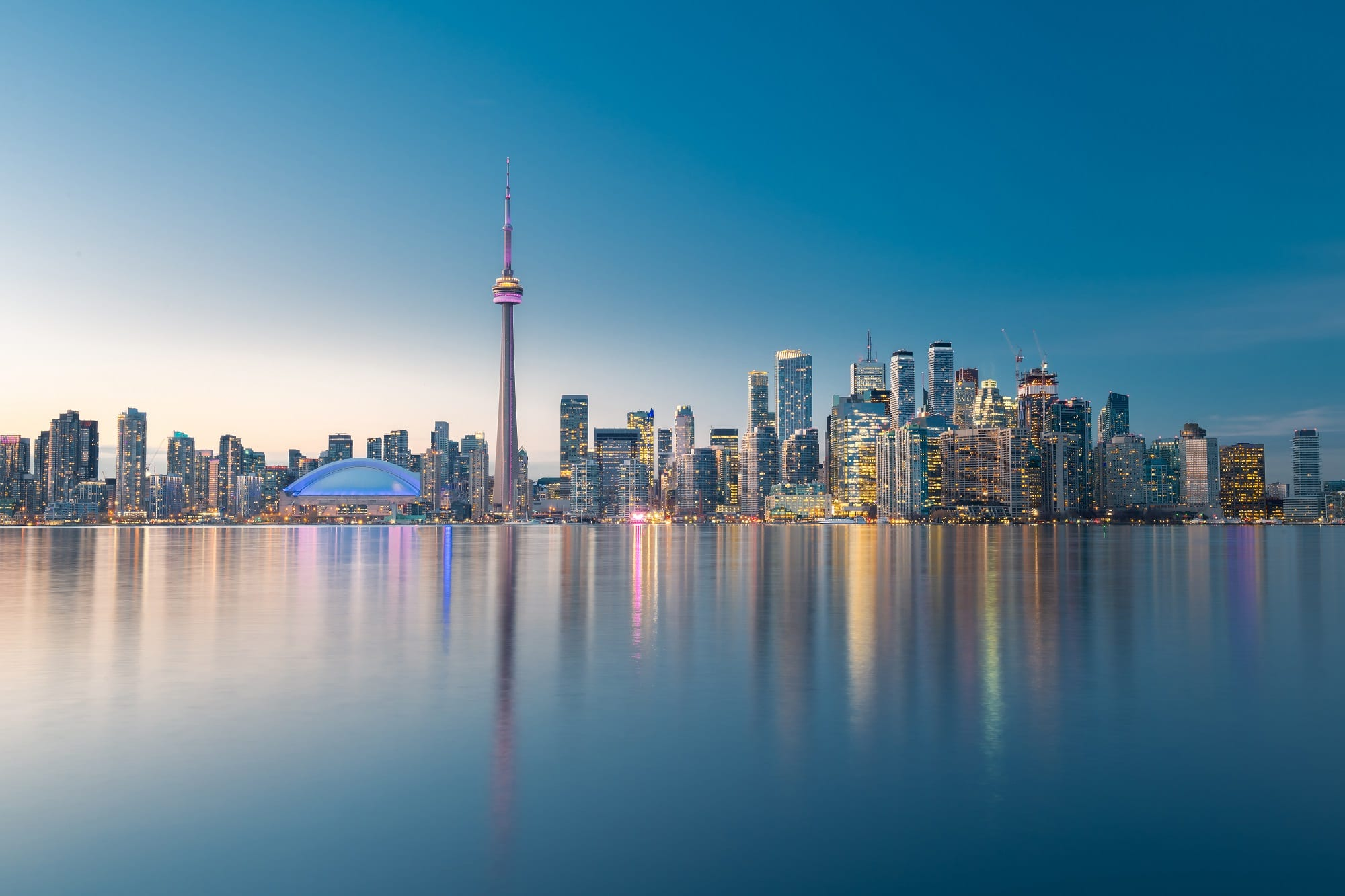 Toronto city skyline, Ontario, Canada looking across the water at buildings at dusk